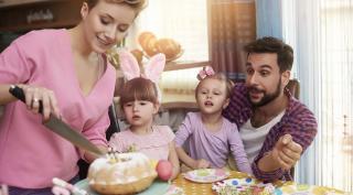Familie mit Mutter, zwei Kindern und Vater beim Kuchenessen.