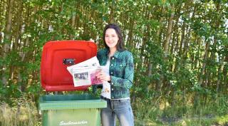 Alice Suppan, Wertstoff-Expertin bei Saubermacher steht neben einer Altpapiertonne