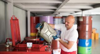 Mann füllt altes Öl in einem Behälter zum recyclen