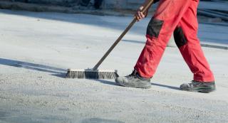 Mitarbeiter beim Reinigen einer Baustelle mit einem Besen
