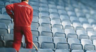Mitarbeiter reinigt zwischen den Sitzplätzen eines Stadions