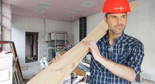 Handwerker mit rotem Helm und Holz auf den Schultern beim entrümpeln