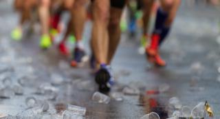 Plastikbecher auf der Straße dahinter Sportler beim Laufen