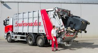 Mitarbeiter entleert Tonne in LKW