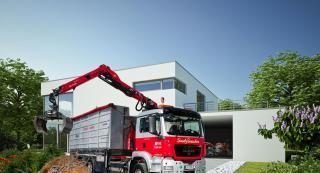 LKW im Einsatz beim Grünschnitt vor einem Haus