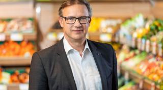 Mann stehend vor einem Gemüseregal eines Supermarkts.
