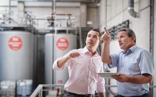 Zwei Männer in einer Saubermacher Anlage einer zeigt auf etwas
