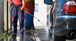 Saubermacher employee cleans a vehicle with a pressure washer.