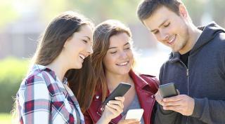 drei junge Menschen mit Smartphone