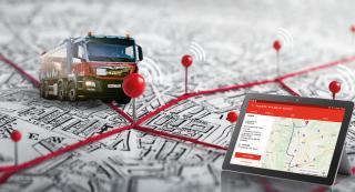 Saubermacher-LKW auf Karte mit Koordinaten und einem Smartphone.