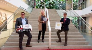 Harald Gorucan, Annemarie Gräßler und Vorstandsvorsitzender Ralf Mittermayr mit dem Staatspreis Familie an der Stiege des Saubermacher Ecoports.