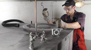 Saubermacher-Mitarbeiter reinigt Öltank