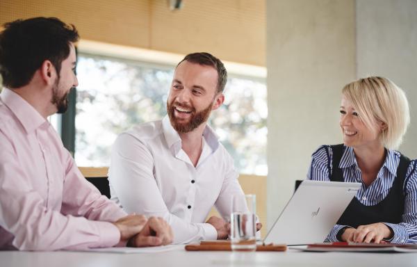 Drei Mitarbeiter am Tisch lachend