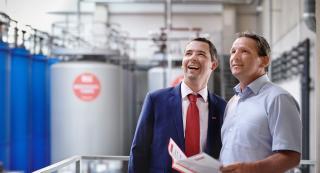 Zwei Männer schauen in einer Anlage beide sehen in eine Richtung
